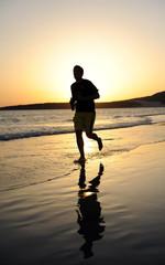 Hombre corriendo al atardecer por la playa