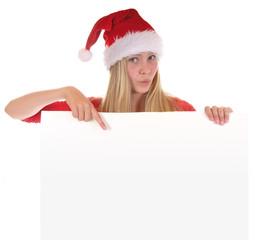 Hübsches Mädchen mit Nikolausmütze deutet auf leere Tafel