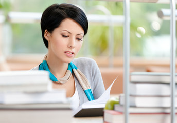 Woman surrounded with piles of books reads sitting at the table