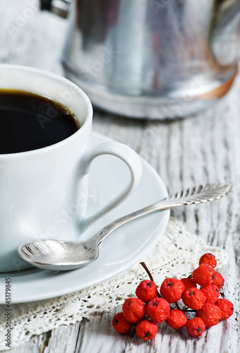 Cup of coffee and red rowan berries