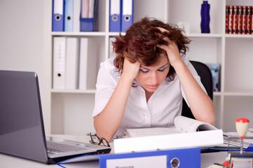Gestresste junge Frau am Schreibtisch