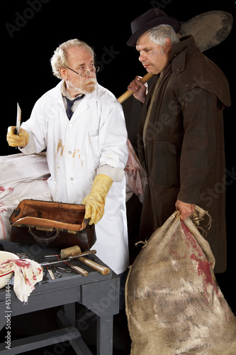 Grave robber and evil doctor with bloody cleaver exchange glance