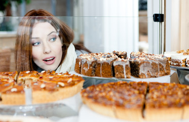 Woman in scarf looking at the bakery glass case