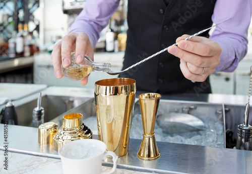 Bartender is adding ingredient in shaker