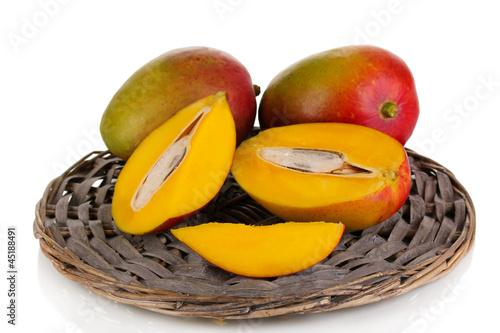Ripe appetizing mango on wicker cradle isolated on white
