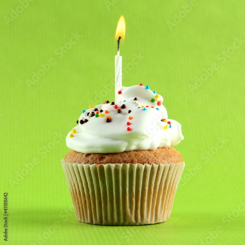 tasty birthday cupcake with candle, on green background
