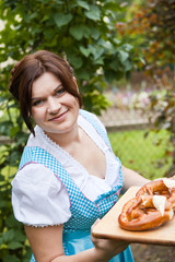 Happy beautiful woman in dirndl dress holding bread