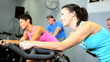 Gym Members Riding Exercise Bicycle