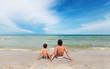 Отец и сын сидят на пляже.