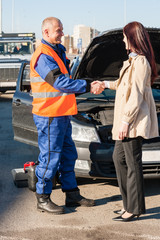 Woman greeting mechanic after her car breakdown