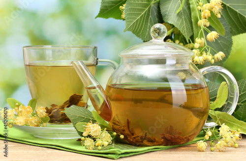 teapot and cup with linden tea and flowers