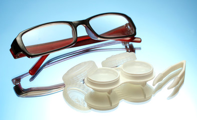 glasses, contact lenses in containers and tweezers