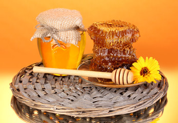 Jar of honey and honeycomb on orange background