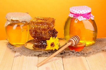 Jars of honey and honeycomb on wooden table on orange