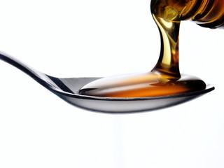 Vertiendo miel en una cuchara,cucharada de miel.