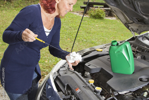 Cute woman checking level of oil on a car engine dipstick