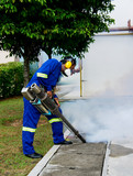 unidentified worker fogging for dengue control