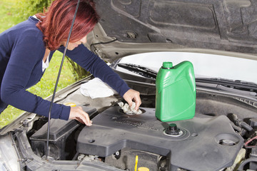 Woman is cleaning car motor cover after adding oil