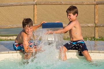 Zwei Jungen spritzen mit Wasser am Swimmingpool - Wasserschlacht