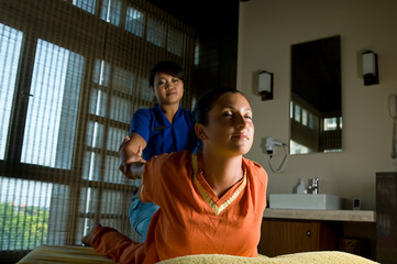 Asian woman Thai massaging beautiful adult woman at spa salon