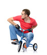 Cool man in glasses on a children's bicycle, white background