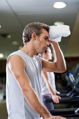 Man Wiping Sweat With Towel At Health Club