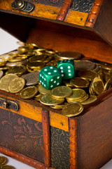 Money coins in a chest with dices