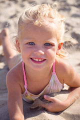 девочка лежит на песке у моря