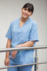 Nurse smiling while leaning against railing