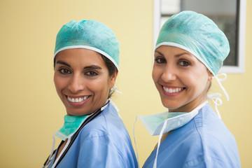 Two happy women wearing scrubs in hospital room