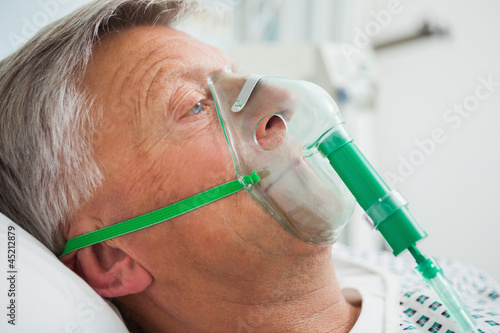 Man in bed with oxygen mask