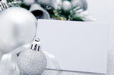 Silver christmas baubles with empty card as copy space