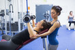 Woman lifting weights and her trainer
