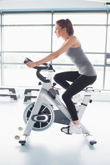 Woman energetically riding exercise bike