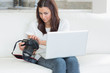 Woman looking at laptop while holding a camera
