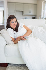 Woman lying on the couch while watching television