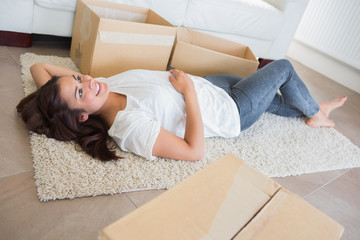 Woman lying on the carpet surrounded by moving boxes