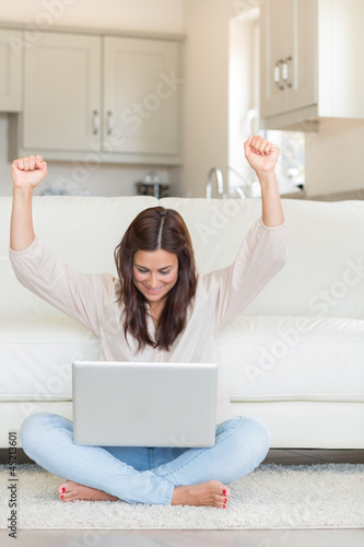 Woman celebrating in front of laptop