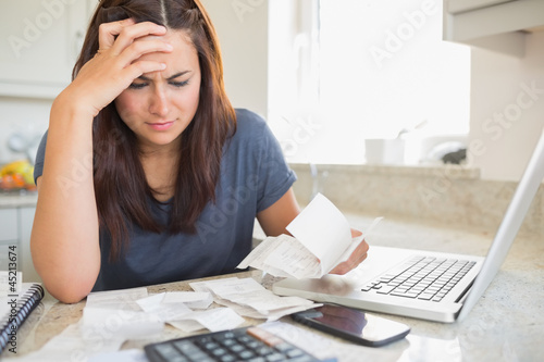 Brunette looking worried over bills
