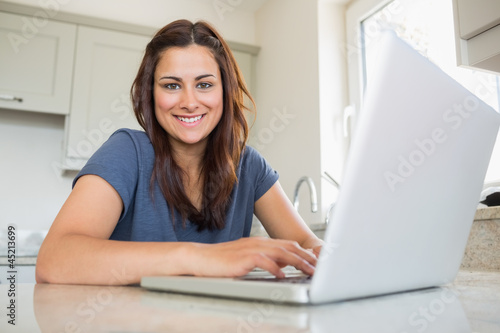 Woman smiling and using laptop