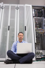 Man sitting in front of servers with his laptop