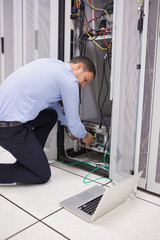 Man doing maintenance and fixing wires on server