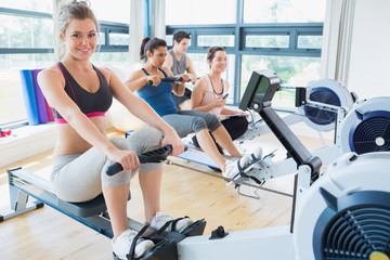 Smiling woman on rowing machine with others