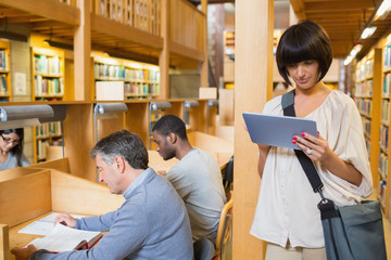 Woman looking at her tablet pc while other people are reading