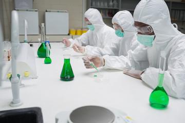 Chemists testing green liquid in petri dishes