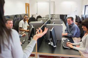 Teacher talking to group in computer room