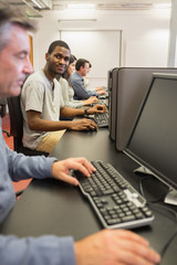 Smiling young man at computer class