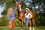Two Beautiful Smiling Cowgirls with horse