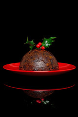 Christmas pudding with holly on black background