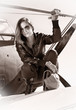 Beautiful girl in black jacket standing on a war aircraft.